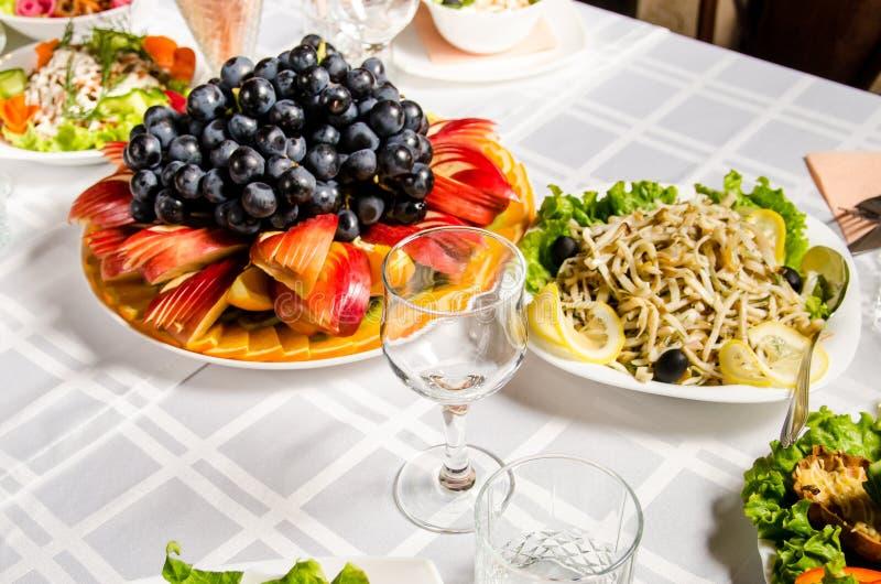 Tabell som fodras med variation av disk som höjdpunkten är maträtten från med skivad frukt arkivfoto