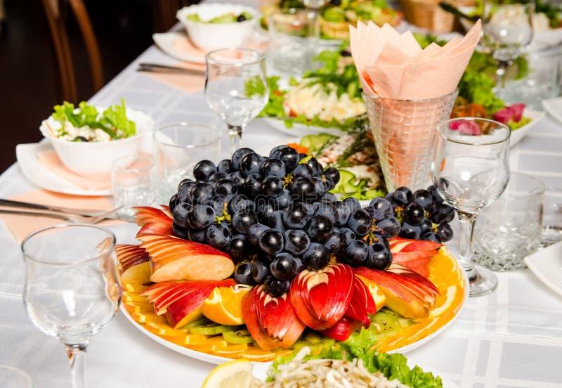 Tabell som fodras med variation av disk som höjdpunkten är maträtten från med skivad frukt arkivbild