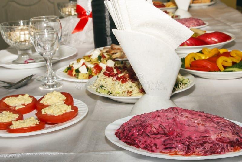 Tabell som tjänas som med mat och bestick Banketttabell för gäster Tomma rena vinexponeringsglas och plattor med det nya mellanmå royaltyfria bilder