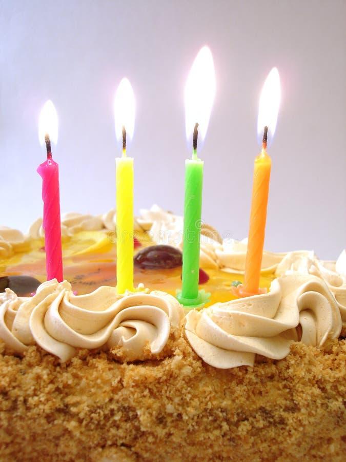 Tabella celebratoria (torta di compleanno e candele colorate) immagine stock