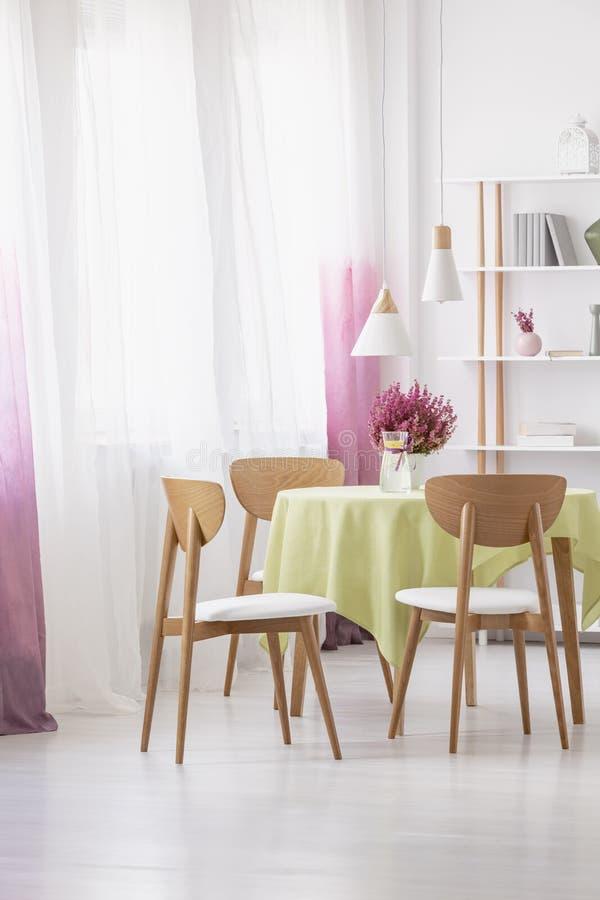 Tabella con acqua del limone, l'erica fresca e la tovaglia verde in foto reale di sala da pranzo interna con le lampade, finestra fotografia stock libera da diritti
