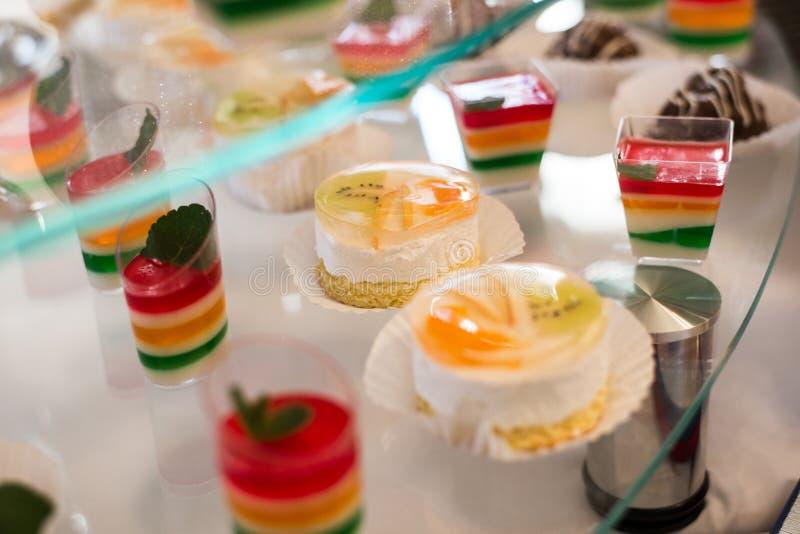Tabella con i dolci, torta di compleanno, cocktail, pasticcerie immagine stock