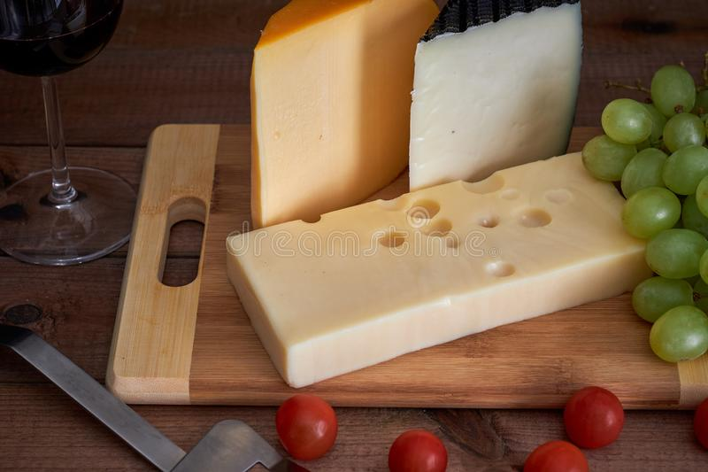 Tabella con i formaggi ed il vetro di vino differenti su fondo scuro fotografie stock