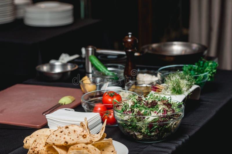 Tabella con i prodotti per i taci Il cuoco unico al ristorante sta andando produrre i taci piccanti del gamberetto con insalata d fotografia stock libera da diritti