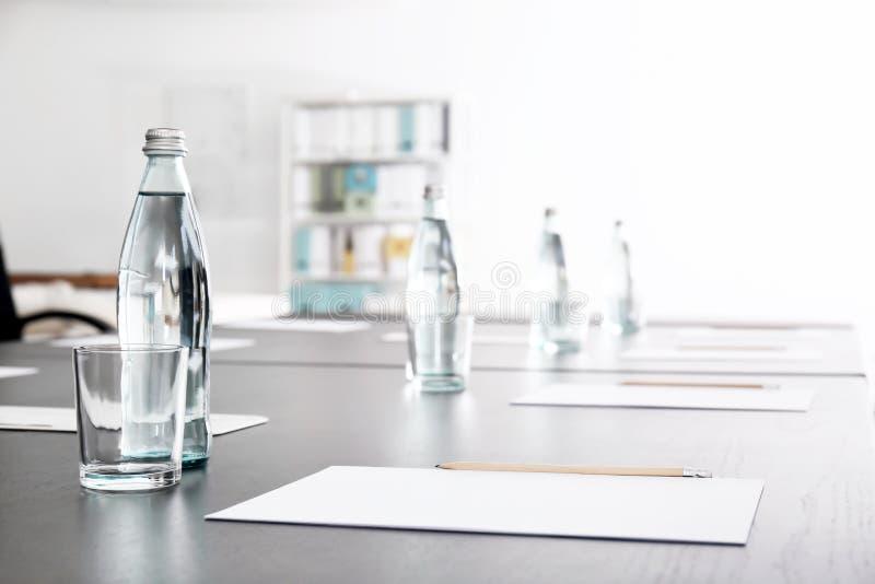 Tabella con le bottiglie di acqua e dei fogli di carta per la riunione d'affari nella sala per conferenze fotografia stock libera da diritti