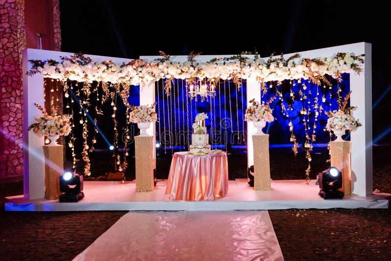Tabella con una torta nunziale, le candele, la luce ed i fiori Decorazione di cerimonia nuziale fotografia stock libera da diritti