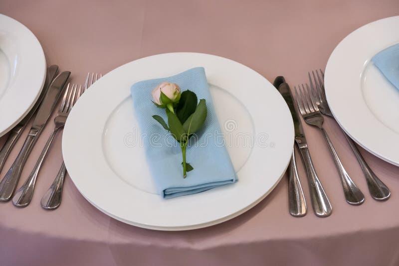 Tabella con una tovaglia rosa, servita e decorata con le rose rosa immagini stock libere da diritti
