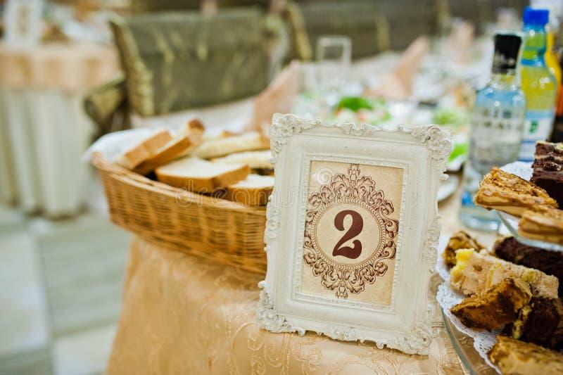 Tabella del ricevimento nuziale con alimento delizioso ed il numero 2 immagini stock