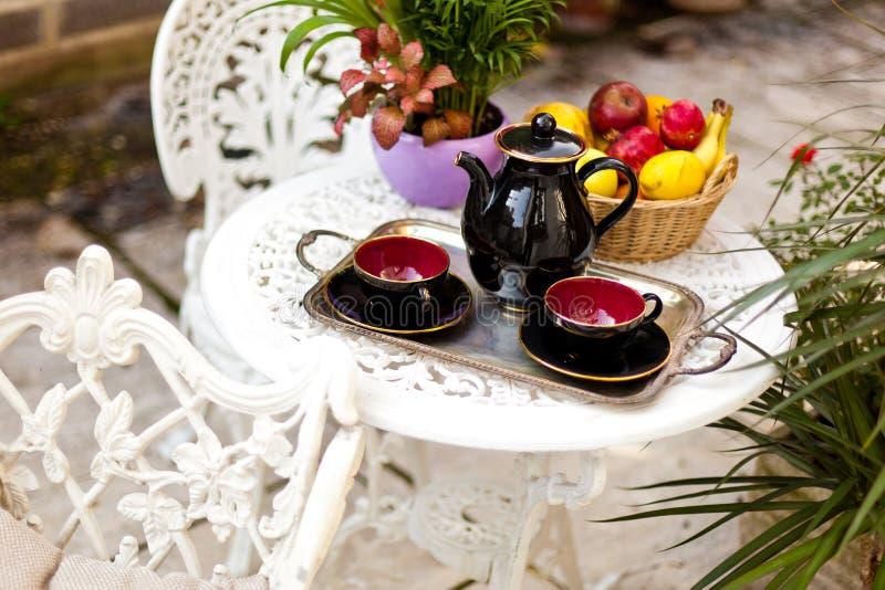Tabella dell'annata con l'insieme di tè e frutta nel giardino fotografia stock libera da diritti