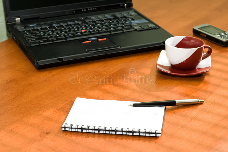 Tabella dell'ufficio con il computer portatile, taccuino immagini stock libere da diritti