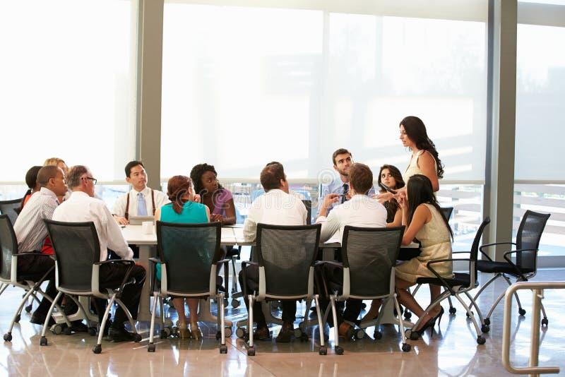Tabella della sala del consiglio di Addressing Meeting Around della donna di affari fotografie stock libere da diritti
