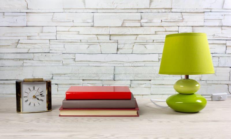 Tabella di legno bianca con i libri una lampada e un orologio immagini stock