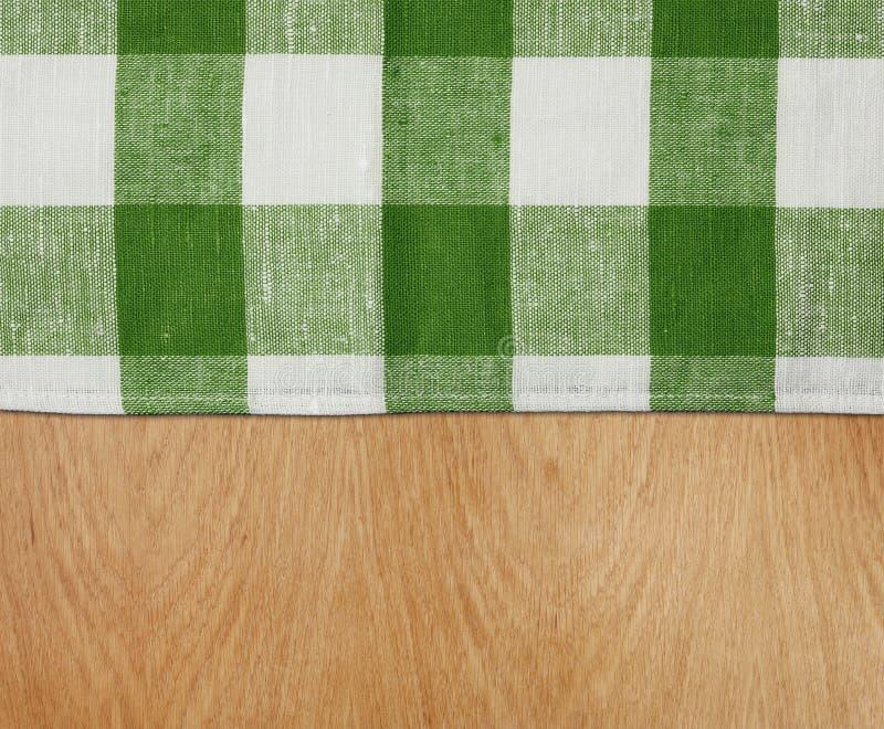 Tabella di legno con la tovaglia verde del percalle fotografia stock libera da diritti