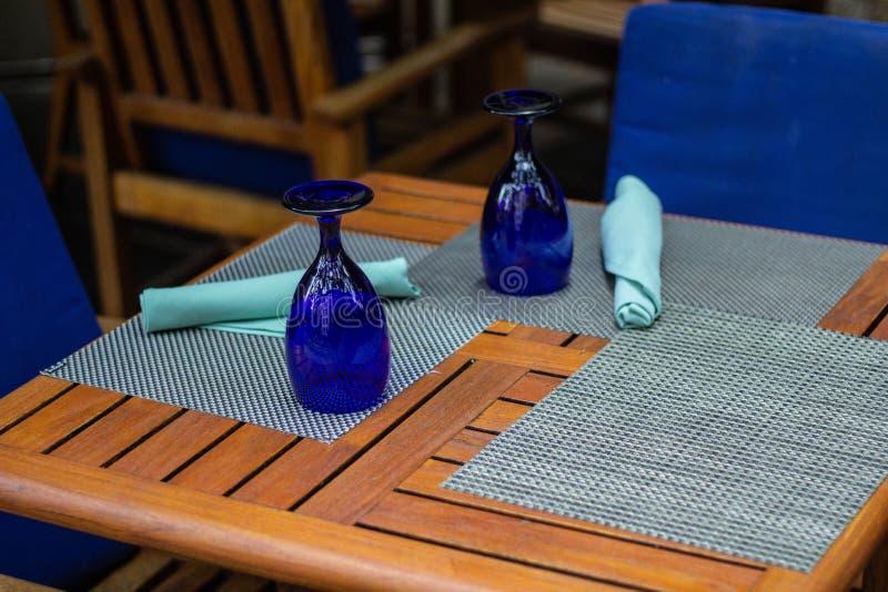 Tabella di legno e due sedie attenuate blu in una sala da pranzo immagini stock