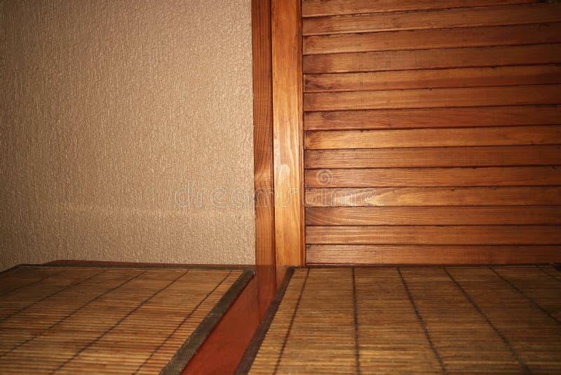 Tabella e parete con la porta di legno verticale e linee orizzontali come fondo immagini stock