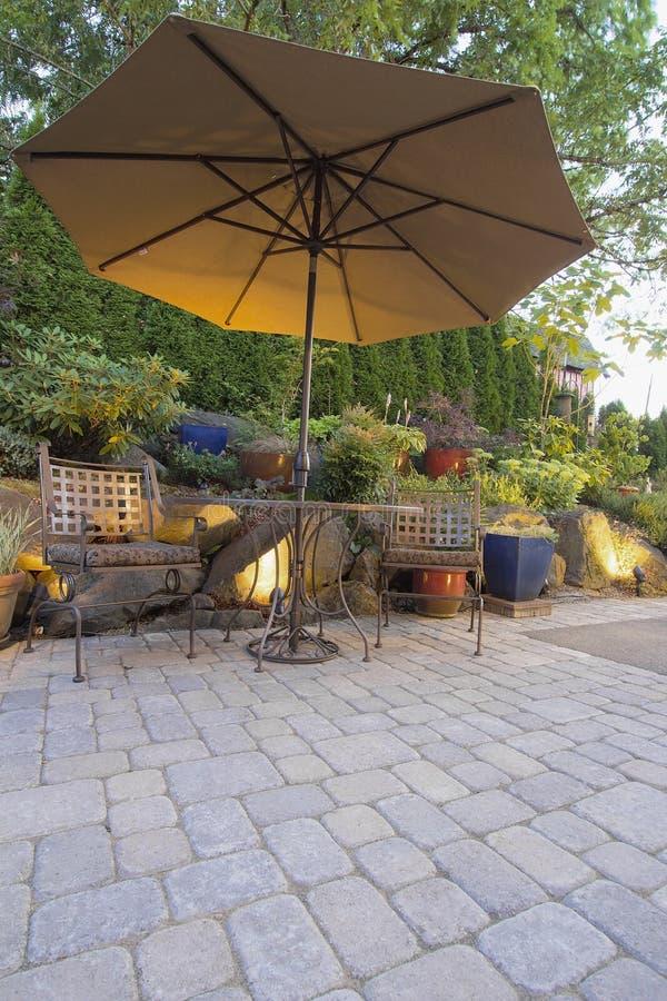 Tabella e presidenze del patio del giardino con l'ombrello fotografia stock