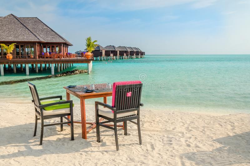 Tabella e sedie al ristorante ai precedenti dei bungalow dell'acqua, isola delle Maldive immagine stock libera da diritti