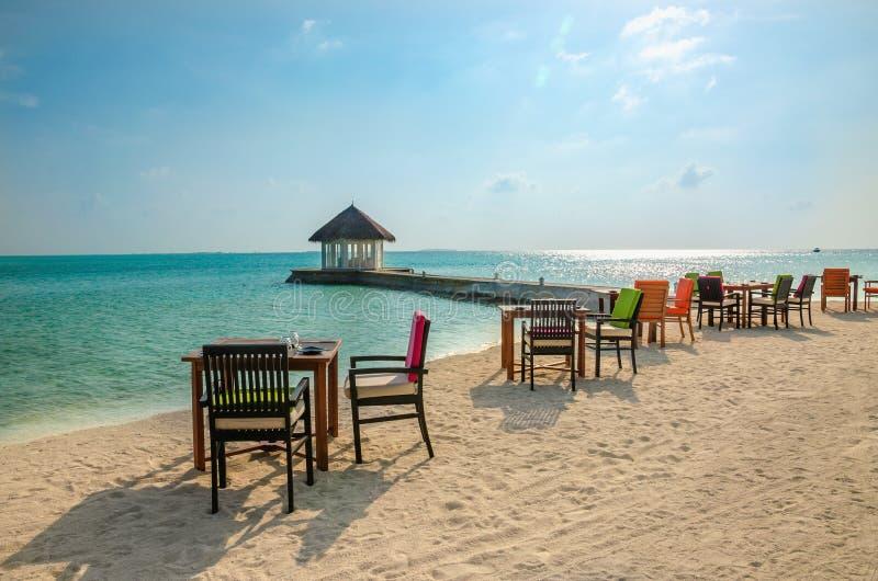 Tabella e sedie al ristorante ai precedenti dei bungalow dell'acqua, isola delle Maldive fotografia stock