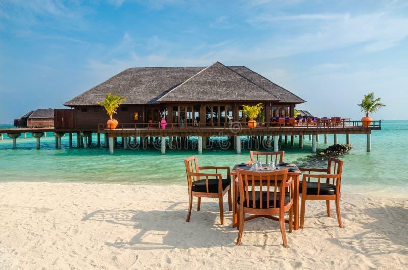 Tabella e sedie al ristorante ai precedenti dei bungalow dell'acqua, isola delle Maldive fotografie stock