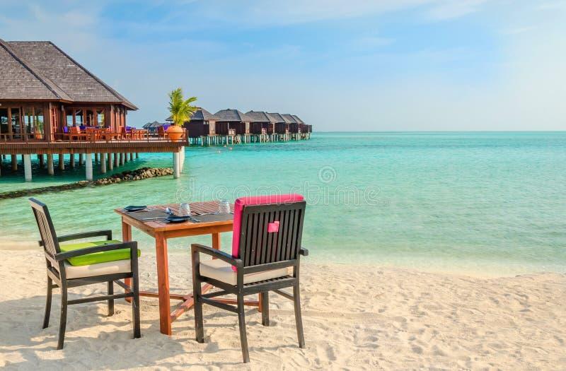 Tabella e sedie al ristorante ai precedenti dei bungalow dell'acqua, Maldive fotografie stock libere da diritti