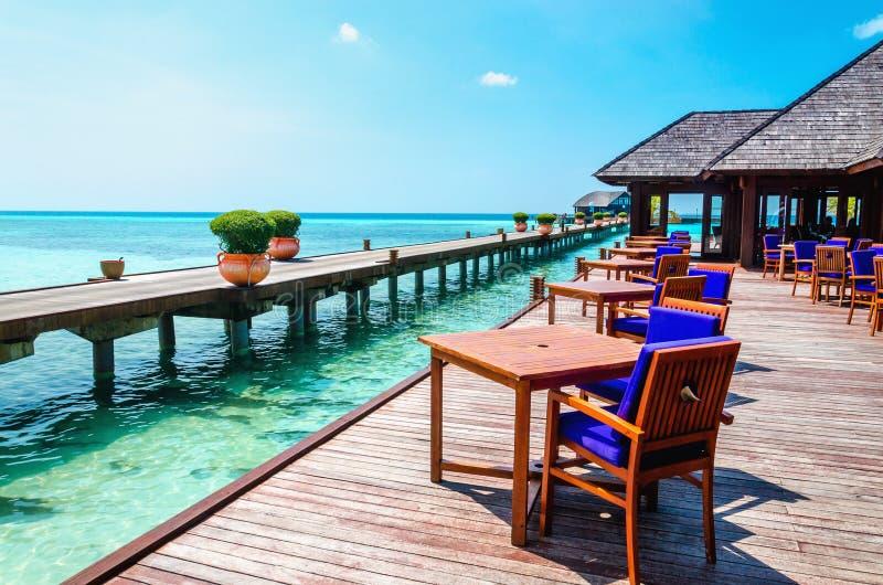 Tabella e sedie al ristorante dell'acqua ai precedenti del cielo blu nell'isola delle Maldive immagini stock