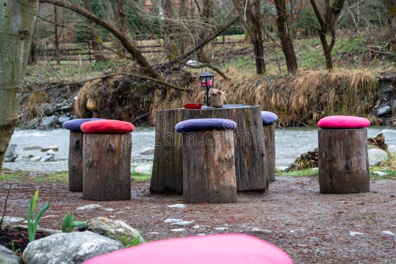 Tabella e sedie fatte dai ceppi dell'albero, con i cuscini variopinti su ogni ceppo/sedia, vicino ad un fiume Concetto per i picn fotografia stock