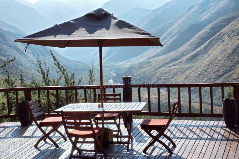 Tabella e sedie sotto l'ombrello sul terrazzo contro la montagna blu fotografie stock