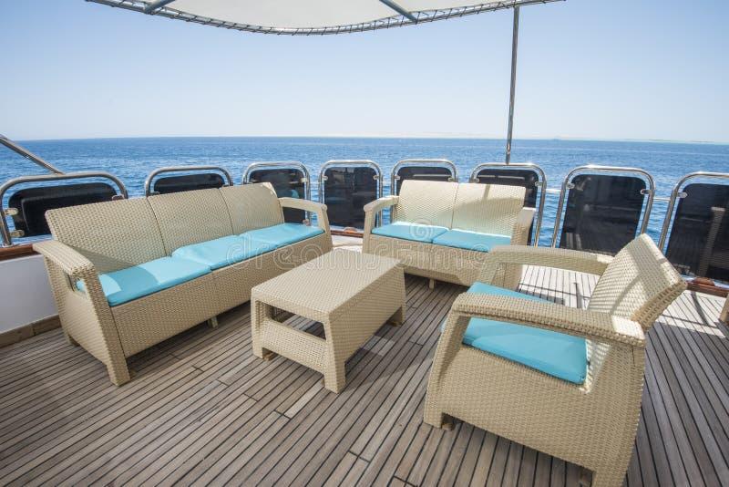 Tabella e sedie sulla piattaforma di un yacht di lusso del motore fotografia stock libera da diritti