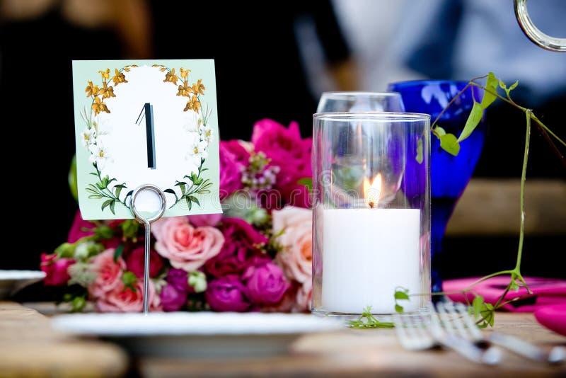 Tabella 1 e un mazzo dei fiori con una candela accesa durante la celebrazione di nozze immagini stock libere da diritti
