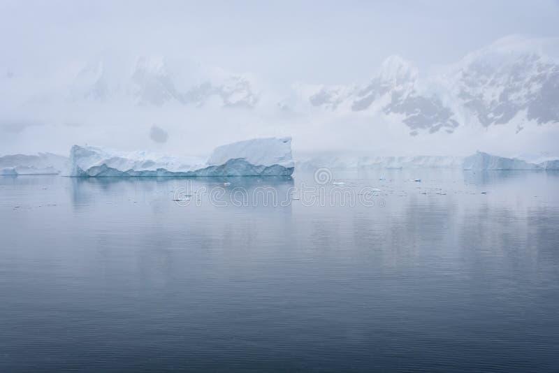 Tabellarischer Eisberg, der in einen ruhigen Paradise-Hafen, gegen einen nebeligen Gebirgshintergrund, die Antarktis schwimmt lizenzfreies stockbild