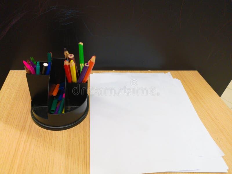 Tabelle con le penne colorate nei disegni dei bambini dell'aula della scuola sulla parete Nessuna gente Movimento lento La tavola immagini stock libere da diritti