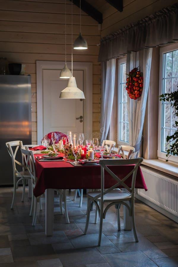 Tabelle diente für Weihnachtsessen, festliche Einstellung mit Dekorationen, brennende Kerzen und Tannenbaumniederlassungen lizenzfreies stockfoto
