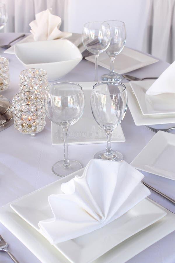 Tabelle diente mit Platten und Weingläsern des weißen Quadrats stockfotografie