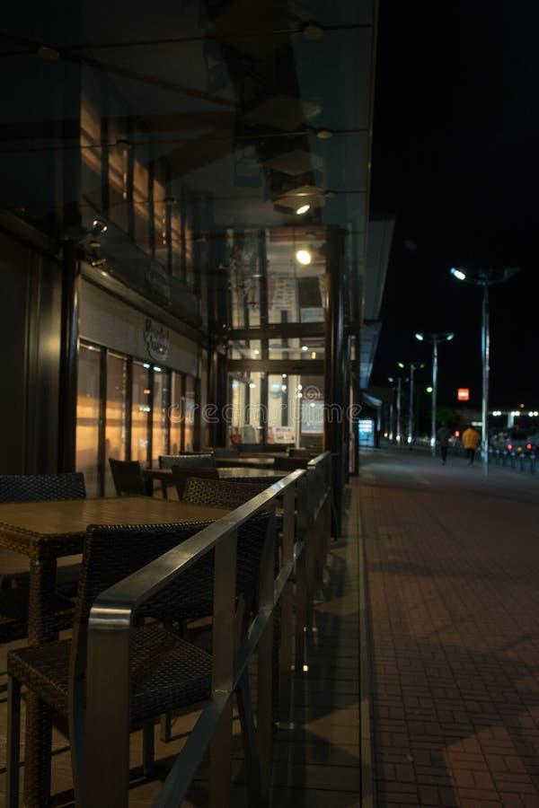 Tabelle e sedie ad un caffe di notte, sedile del terrazzo fotografie stock libere da diritti