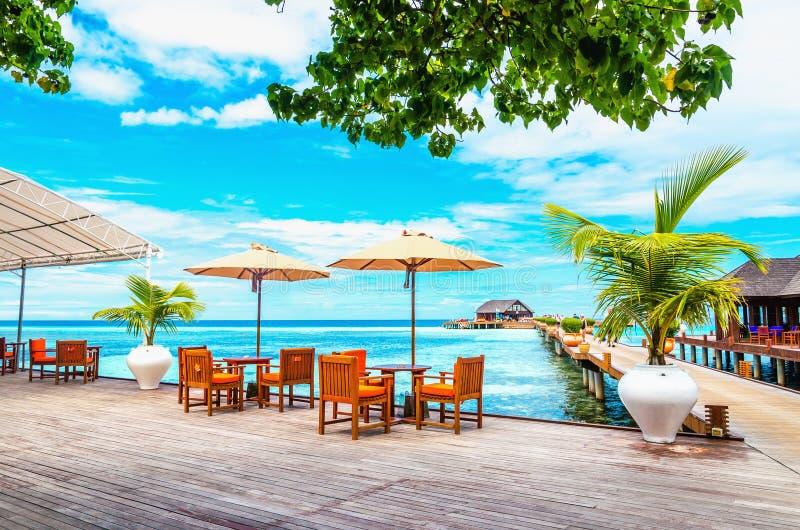 Tabelle e sedie con gli ombrelloni su un pilastro di legno contro l'acqua azzurrata dell'oceano e dei bungalow di legno sul fotografia stock