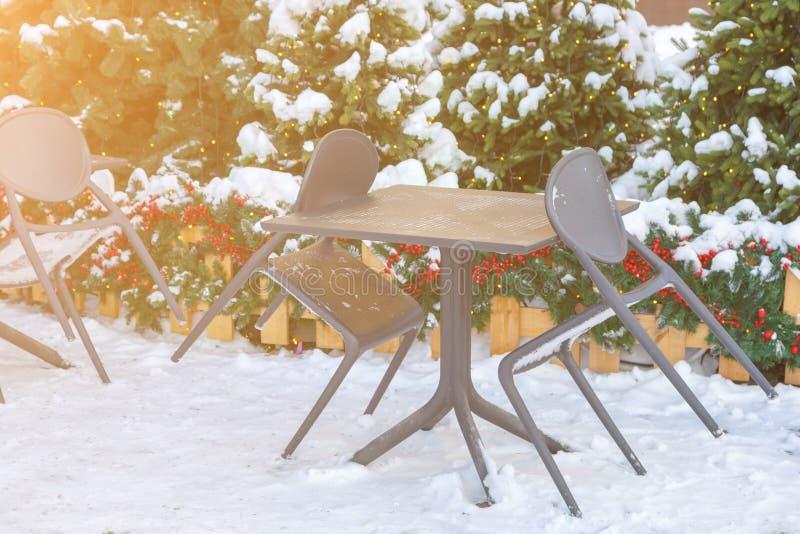 Tabelle e sedie di un caffè della via coperto di neve durante le feste del nuovo anno fotografia stock libera da diritti