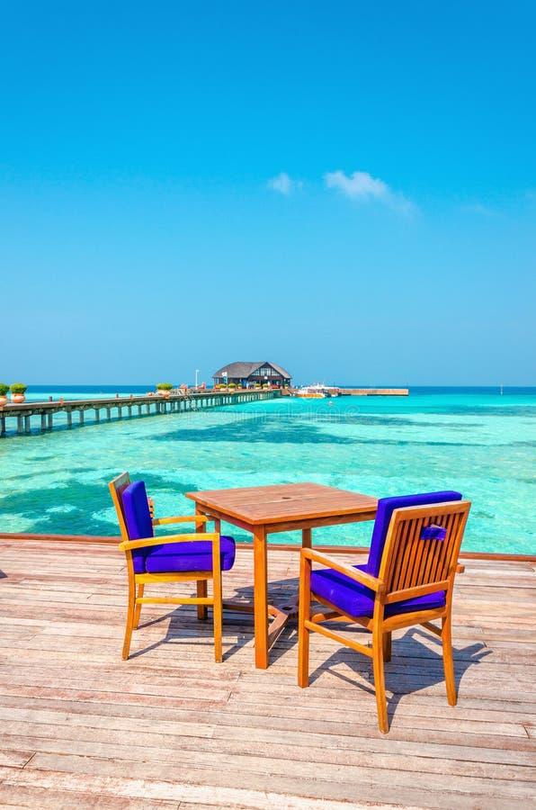 Tabelle e sedie in un ristorante di legno sui trampoli sui precedenti di acqua azzurrata e del cielo soleggiato fotografia stock libera da diritti