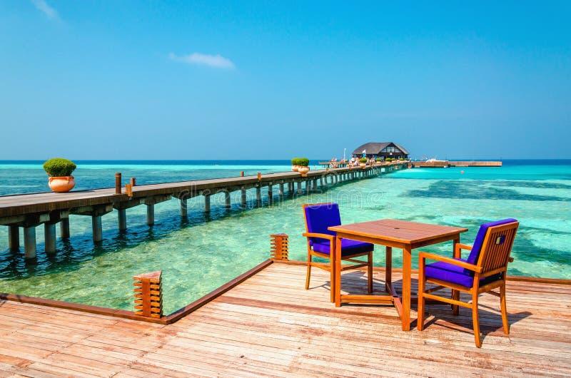 Tabelle e sedie in un ristorante di legno sui trampoli sui precedenti di acqua azzurrata e del cielo soleggiato fotografie stock