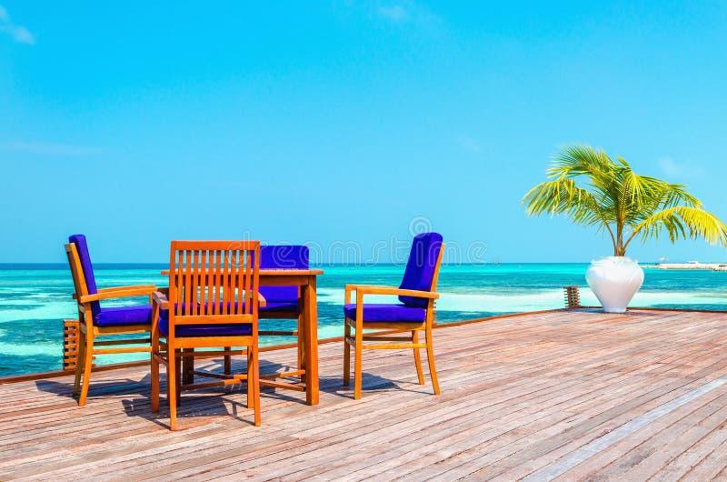 Tabelle e sedie in un ristorante di legno sui trampoli sui precedenti di acqua e di cielo blu azzurrati immagine stock