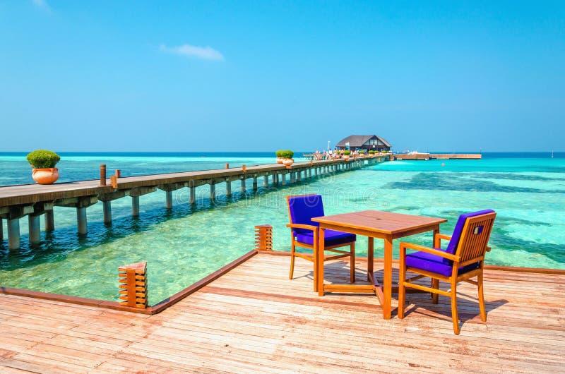 Tabelle e sedie in un ristorante di legno sui trampoli sui precedenti di acqua e di cielo blu azzurrati fotografie stock libere da diritti