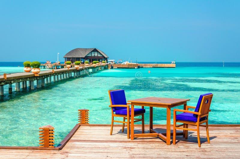Tabelle e sedie in un ristorante di legno sui trampoli sui precedenti di acqua e di cielo blu azzurrati immagine stock libera da diritti
