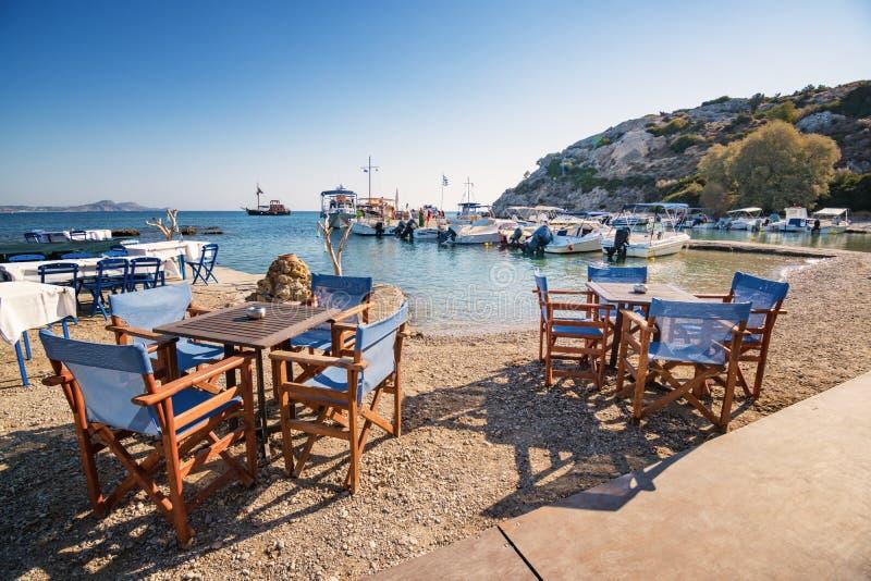 Tabelle e sedie vicino al porto in Kolymbia Rodi, Grecia immagini stock