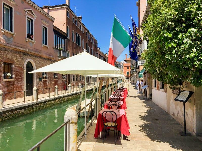 Tabelle ed ombrelli di un ristorante precisato lungo una strada calma del canale con la bandiera italiana qui sopra fotografie stock libere da diritti