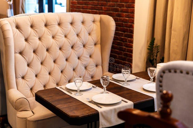Tabelle in einem Café, dienend in einem Café, ein beige Sofa der Weinlese, Holztisch lizenzfreie stockfotografie