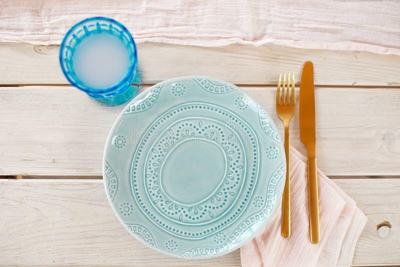 Tabelle für Gäste, verziert mit Kerzen, gedient mit Tischbesteck und Tonware und mit einer blauen Platte der Tischdecke bedeckt u lizenzfreie stockfotos