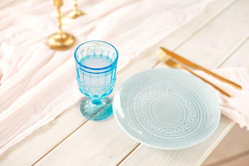 Tabelle für Gäste, verziert mit Kerzen, gedient mit Tischbesteck und Tonware und mit einer blauen Platte der Tischdecke bedeckt u lizenzfreie stockbilder