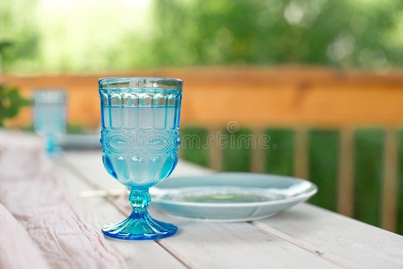Tabelle für Gäste, verziert mit Kerzen, gedient mit Tischbesteck und Tonware und mit einer blauen Platte der Tischdecke bedeckt u stockfotografie