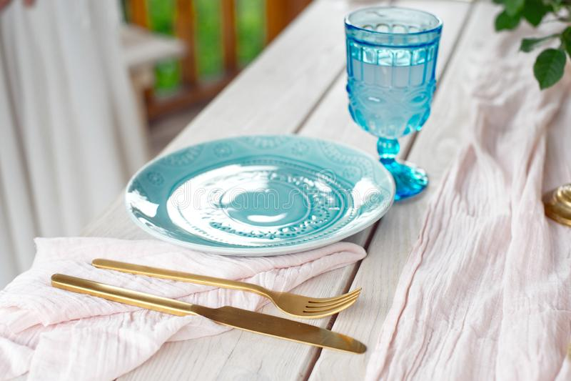 Tabelle für Gäste, verziert mit Kerzen, gedient mit Tischbesteck und Tonware und mit einer blauen Platte der Tischdecke bedeckt u lizenzfreie stockfotografie