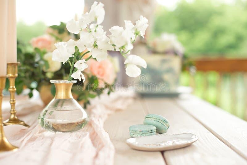 Tabelle für Gäste, verziert mit Kerzen, gedient mit Tischbesteck und Tonware und mit einer blauen Platte der Tischdecke bedeckt u stockfoto