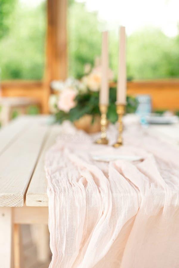 Tabelle für Gäste, verziert mit Kerzen, gedient mit Tischbesteck und Tonware und mit einer blauen Platte der Tischdecke bedeckt u stockbilder